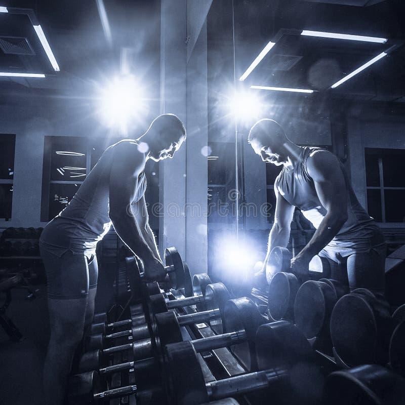 Een sportieve mens in een T-shirt die zich voor een spiegel bevinden neemt domoren in de gymnastiek Gestemd beeld royalty-vrije stock foto