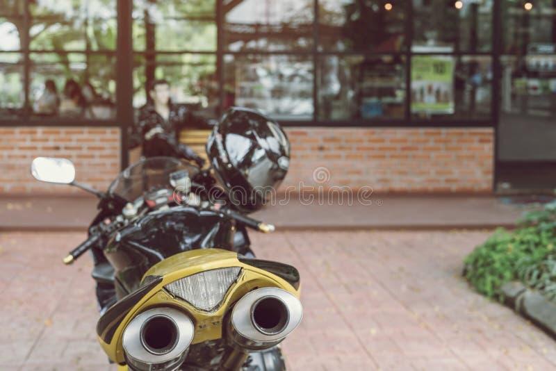Een sportieve motorfiets die voor koffiewinkel wordt geparkeerd stock foto's
