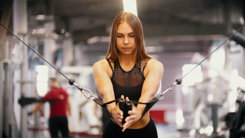 Een sportieve vrouw die in de gymnastiek opleiden die - de handvatten trekken tegen zich - opleidingshanden stock fotografie