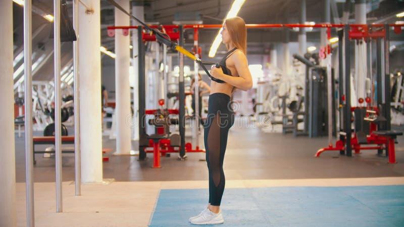 Een sportieve vrouw in sporten kleedt opleiding in de gymnastiek - houdend de handvatten en treft terug te leunen voorbereidingen stock afbeeldingen