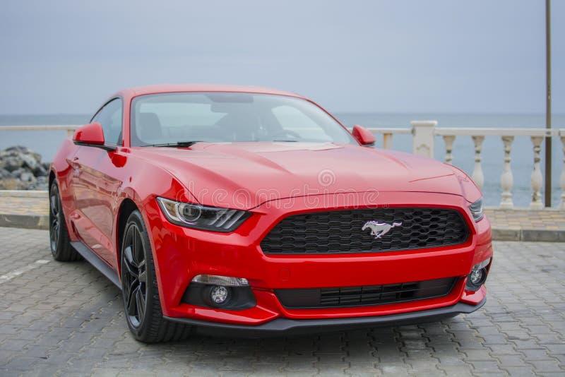 Een sportwagen rode kleur tegen het overzees royalty-vrije stock foto's