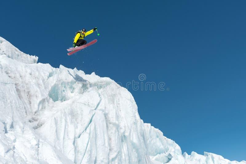 Een springende skiër die van een gletsjer tegen een blauw exorbitant in de bergen springen Het professionele ski?en stock foto
