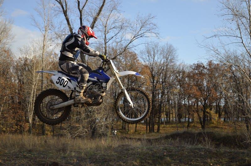 Een sprongruiter op een motorfietsmotocross stock afbeelding