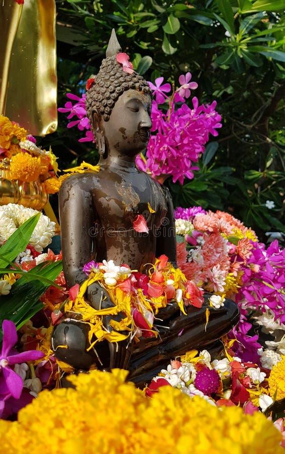 Een standbeeld van brons klein Boedha bij de tempel met natte gele rode bloembloemkronen voor Songkran-festival stock afbeelding