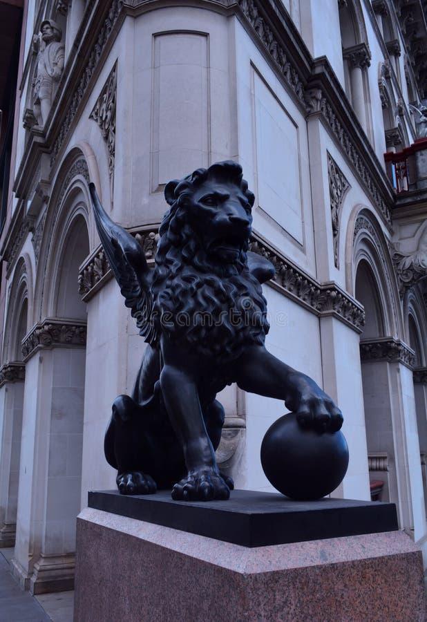 Een standbeeld van een gevleugelde leeuw die een bal, Londen, het Verenigd Koninkrijk houden stock afbeeldingen
