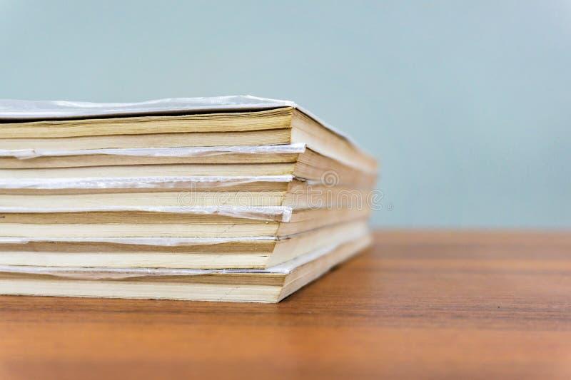 Een stapel boeken ligt op een bruine lijst, zijn de documenten gestapeld close-up stock fotografie