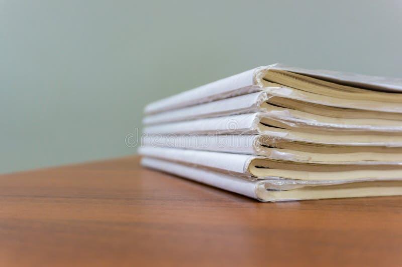 Een stapel boeken ligt op een bruine lijst, zijn de documenten gestapeld close-up royalty-vrije stock foto