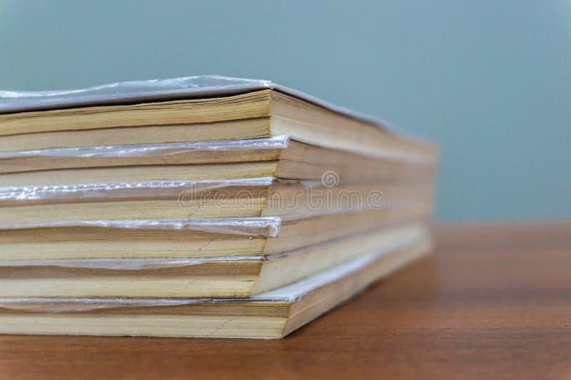 Een stapel boeken ligt op een bruine lijst, zijn de documenten gestapeld close-up stock afbeeldingen