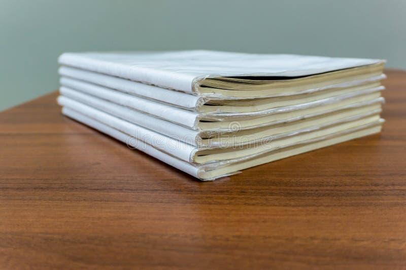 Een stapel boeken ligt op een bruine lijst, zijn de documenten gestapeld close-up stock afbeelding