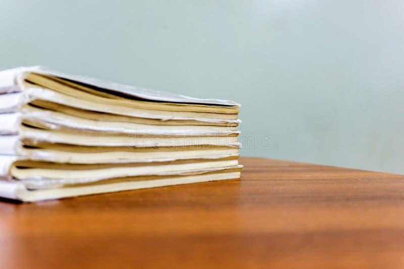 Een stapel boeken ligt op een bruine lijst, zijn de documenten gestapeld close-up royalty-vrije stock afbeeldingen
