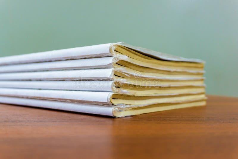 Een stapel boeken ligt op een bruine lijst, zijn de documenten gestapeld close-up stock foto's