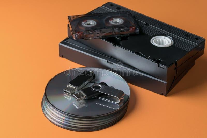 Een stapel compact-discs en video-audio banden en een flits drijven op een oranje achtergrond royalty-vrije stock foto