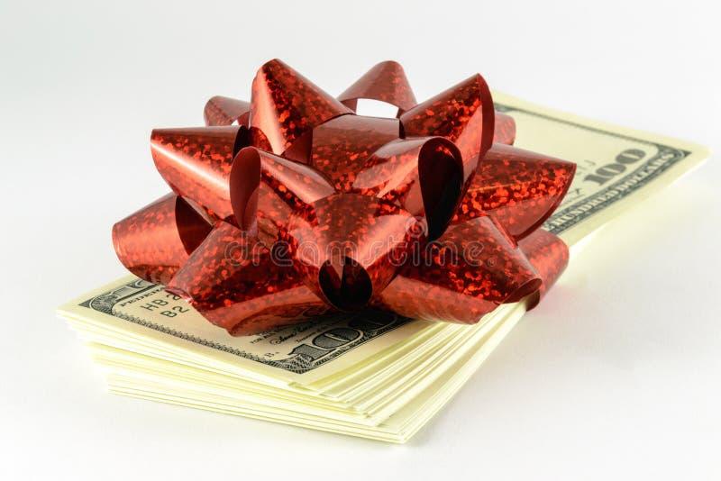 Een stapel dollars en een rode gift buigen stock afbeeldingen