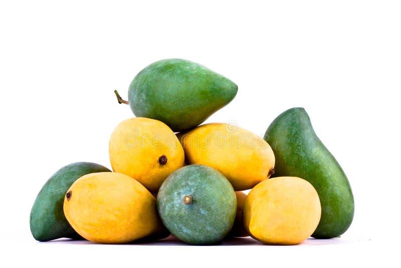 Een stapel gele rijpe mango's en verse groene mango's op wit achtergrond gezond geïsoleerd fruitvoedsel royalty-vrije stock afbeeldingen