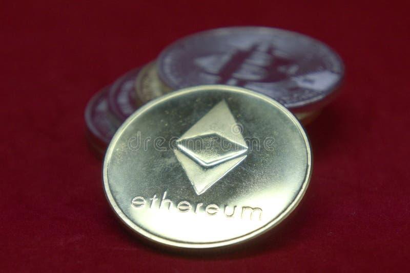 Een stapel gouden en zilveren cryptocurrencymuntstukken met ethereum in de voorzijde op een rode fluweelachtergrond stock afbeeldingen