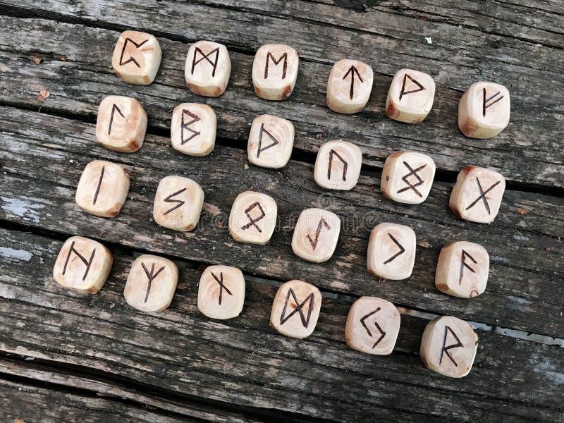 Een stapel houten runen bij bos Houten runen ligt op een oude houten achtergrond De runen worden gesneden van houten blokken Op e stock fotografie