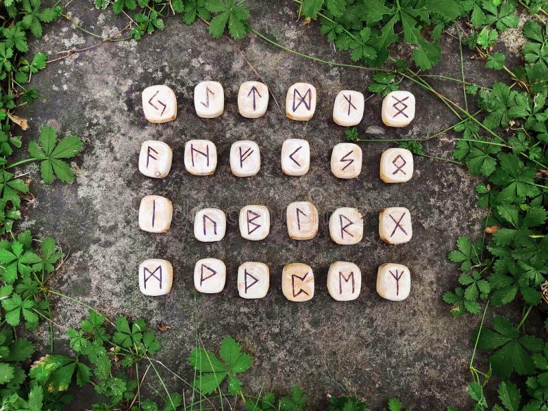 Een stapel houten runen bij bos Houten runen ligt op een rotsachtergrond in het groene gras De runen worden gesneden van houten stock foto