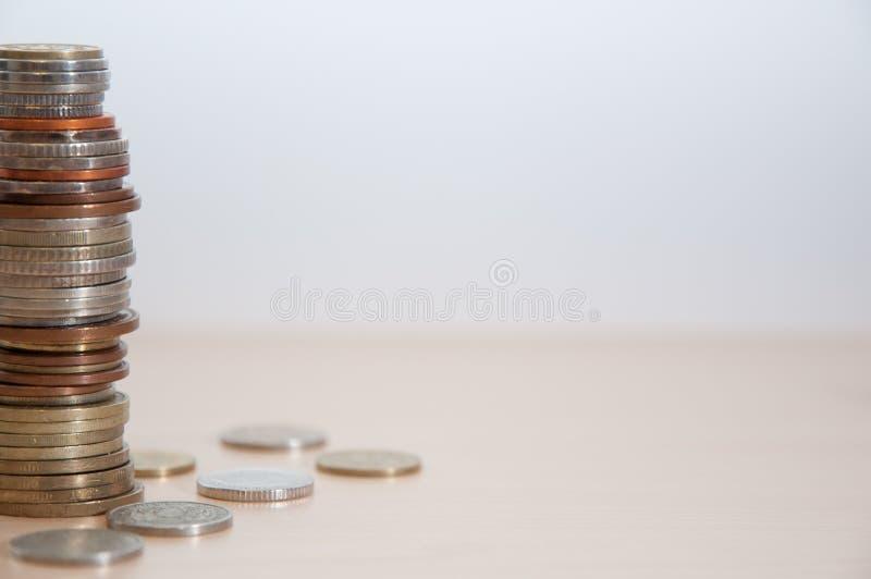 Een stapel muntstukken van verschillende landen, kleur, waardigheid en grootte op de linkerzijde stock fotografie