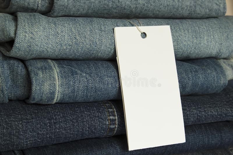 Een stapel nieuwe jeans met het model van de Witboekmarkering stock fotografie