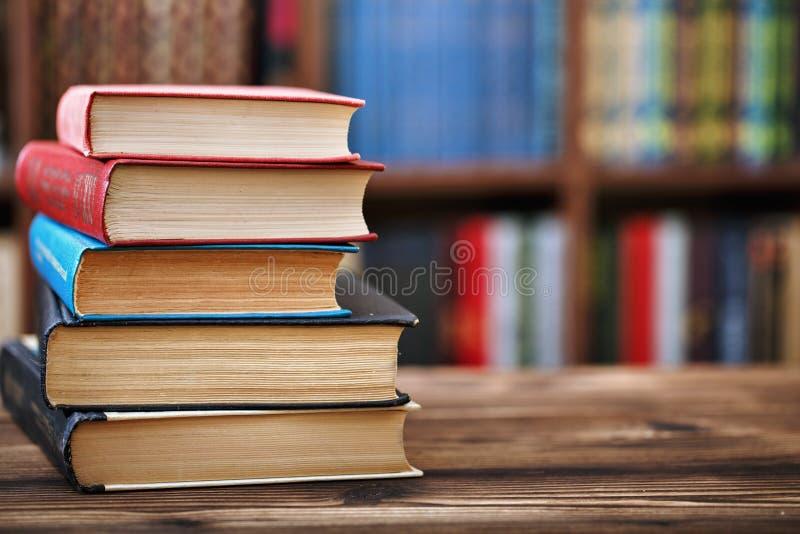 Een stapel oude document boeken op een houten lijst Boekenrekken op de achtergrond Vage achtergrond stock afbeelding