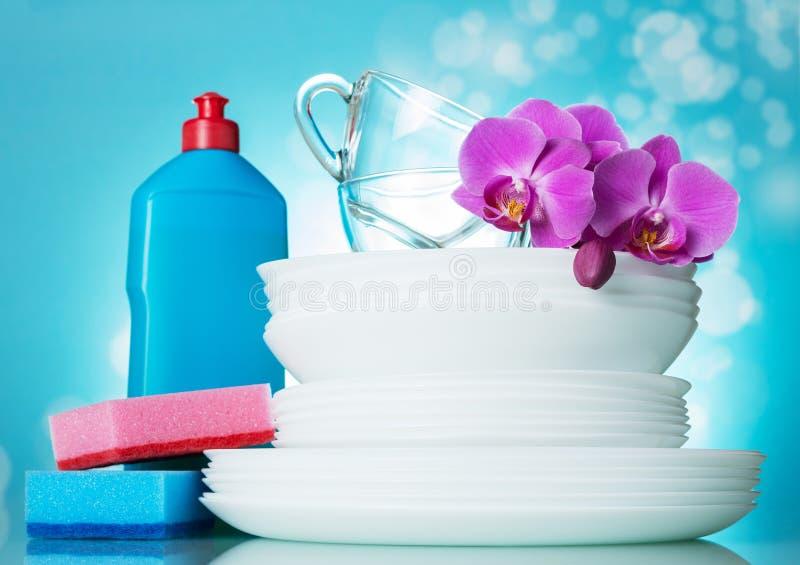 Een stapel schone platen, glas vormt, op hoogste bloem tot een kom, dichtbij detergens en spons op lichtblauw royalty-vrije stock afbeelding