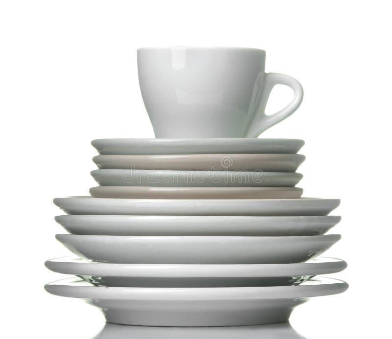 Een stapel schotels dinnerware platen en kop op een wit geïsoleerde achtergrond Close-up stock afbeeldingen