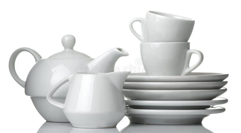 Een stapel schotels dinnerware platen, ketel en kop op een wit geïsoleerde achtergrond Close-up royalty-vrije stock fotografie