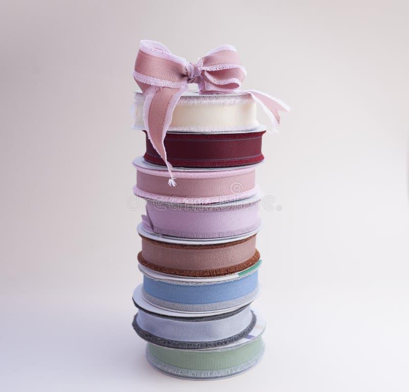 Een stapel spoelen met multi-colored replinten voor decoratie en verpakking van giften en boeketten met boog royalty-vrije stock fotografie