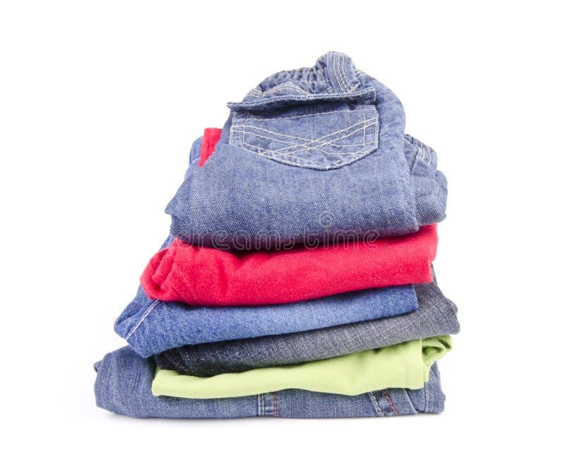 Een stapel van de kleding van kleurrijke kinderen op een wit stock foto