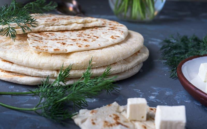Een stapel van eigengemaakte pitabroodjekaas, feta-kaas op een kleine plaat, dilletwijgen royalty-vrije stock foto