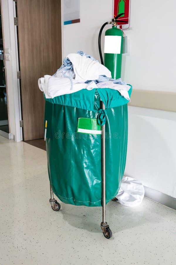 Een stapel van gebruikte kleren in het ziekenhuis beweegbaar karretje met groene bedelaars royalty-vrije stock fotografie