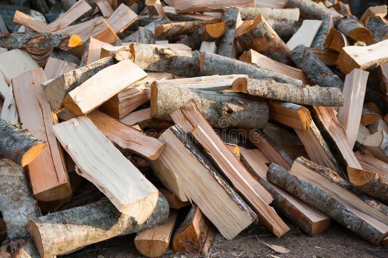 Een stapel van gehakt brandhout ligt op de grond Het materiaal voor het verwarmen stock fotografie