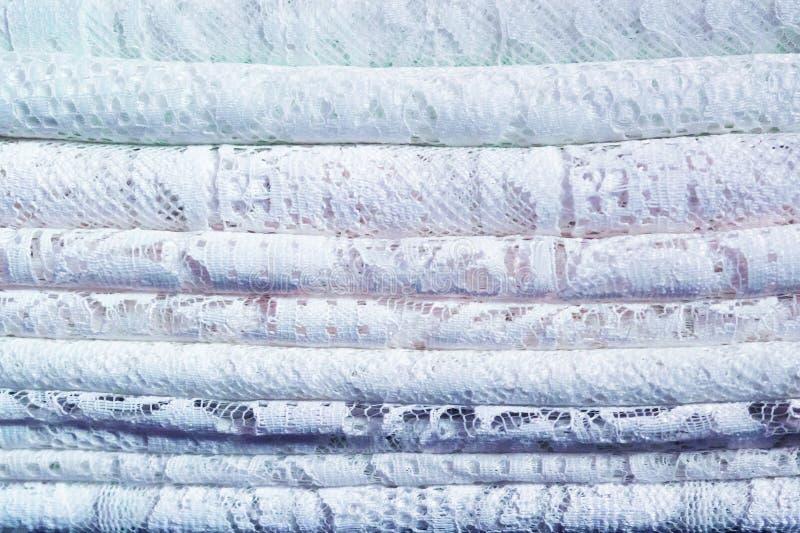 Een stapel van gevoelige traditionele kant textielstoffen met een natuurlijk patroon van wit en blauw stock afbeelding