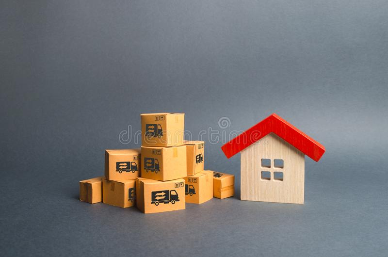Een stapel van kartondozen en een blokhuis Concept het gaan naar een andere huis of stad Bezitsvervoer vracht royalty-vrije stock afbeelding