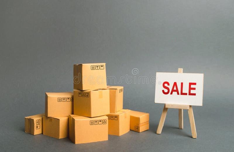 Een stapel van kartondozen en tribune met de woordverkoop verkoop van producten, kortingen op goederen van het uitgaande seizoen  stock fotografie