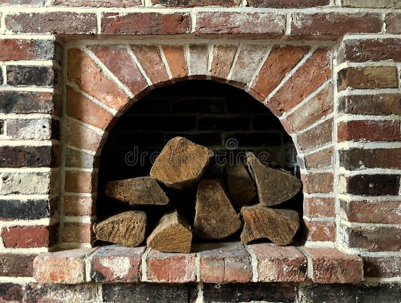 Een stapel van logboeken wordt gestapeld binnen het openen in een muur F van de baksteenopen haard royalty-vrije stock afbeelding