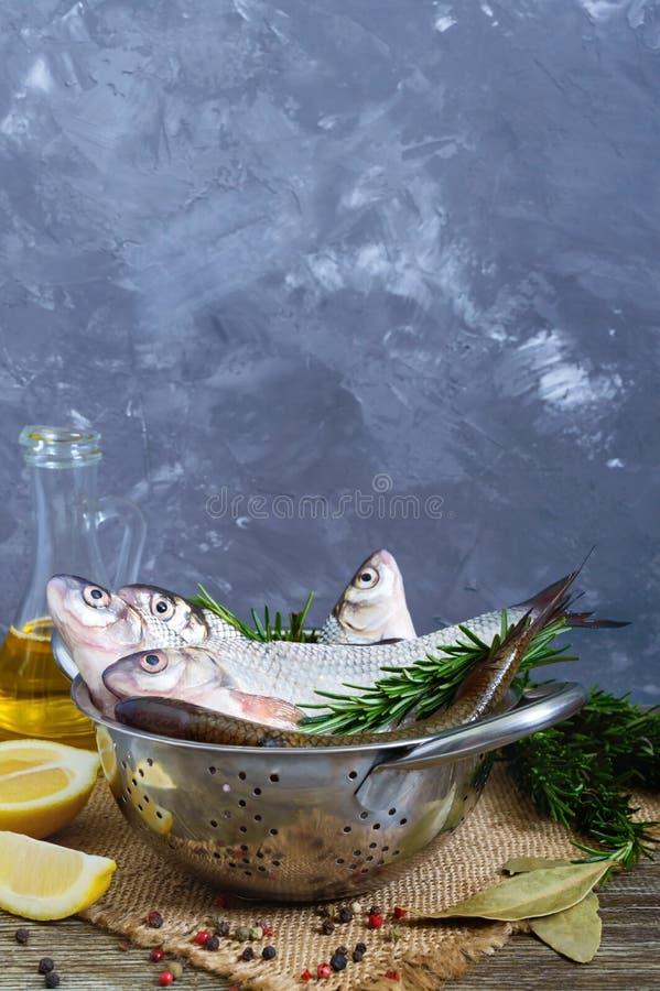 Een stapel van verse ruwe vissen met kruiden, citroen, rozemarijn op een houten achtergrond Verse Vangst royalty-vrije stock foto's