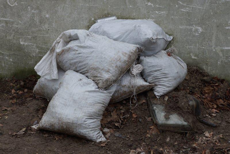 Een stapel van witte vuilniszakken ter plaatse dichtbij de omheining stock fotografie