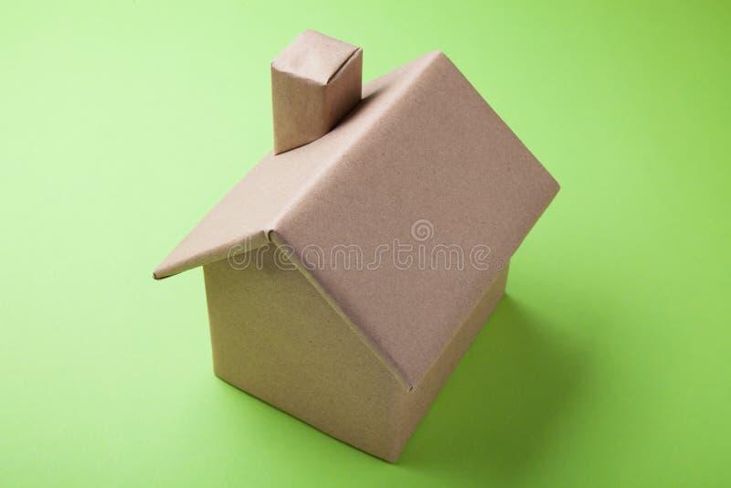 Een steekproef van een woningshuis wordt gemaakt van karton Groene Achtergrond royalty-vrije stock afbeelding