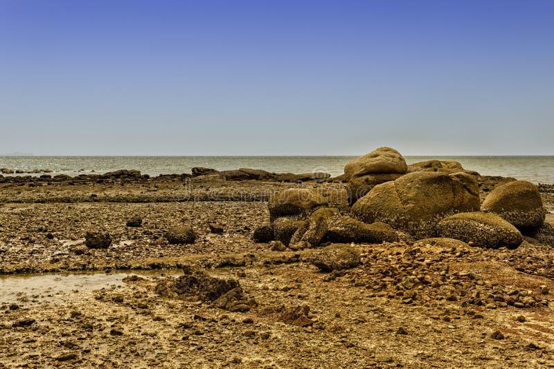 Een steenachtig strand onder een blauwe hemel stock afbeeldingen