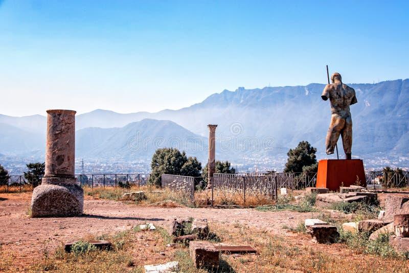 Een steenkolom in de ruïnes van de de steenkolom van stadspompeia en het standbeeld van held in de ruïne van de stad Pompei stock afbeeldingen