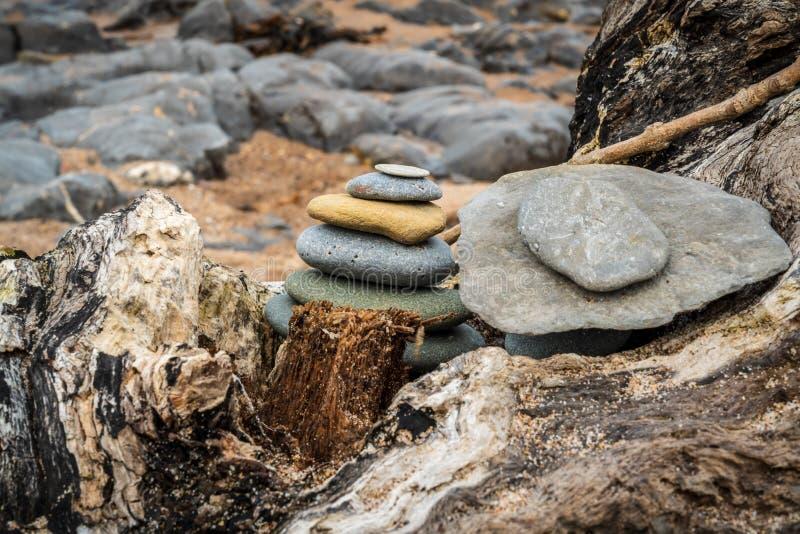 Een steenstapel op een boomboomstam stock fotografie