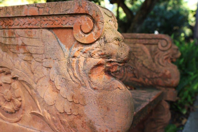 Een steentuinbankje met mythologische creatieve sculpturen royalty-vrije stock foto