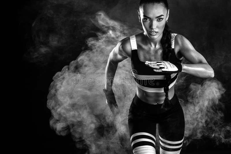 Een sterke atletische, vrouwelijke sprinter, die bij zonsopgang lopen die in het de sportkleding, de fitness en concept van de sp royalty-vrije stock afbeelding