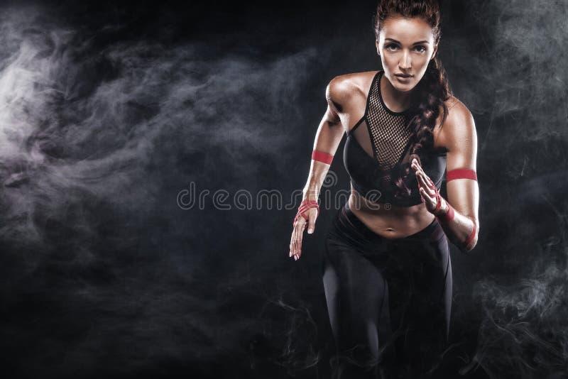 Een sterke atletische, vrouwensprinter, die op zwarte achtergrond lopen die in de sportkleding, de fitness en de sportmotivatie d stock foto