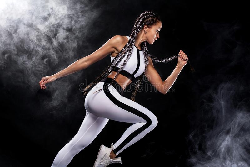 Een sterke atletische, vrouwensprinter, die op zwarte achtergrond lopen die in de sportkleding, de fitness en de sportmotivatie d stock foto's