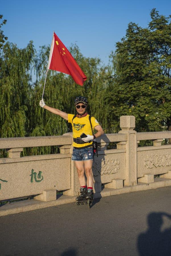 Een sterke schaatsende mens op middelbare leeftijd met een hand die een geel overhemd houden die een blauwe t-shirt dragen en kor stock afbeeldingen