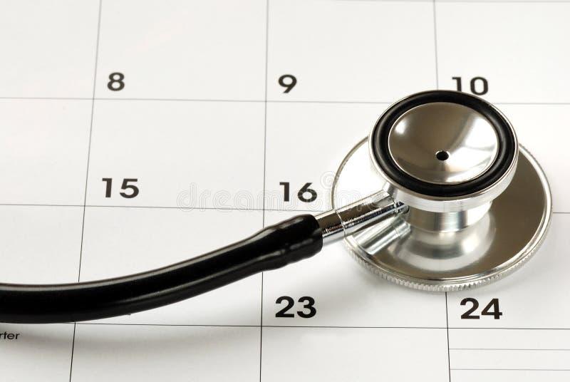 Een stethoscoop op de kalender stock afbeelding