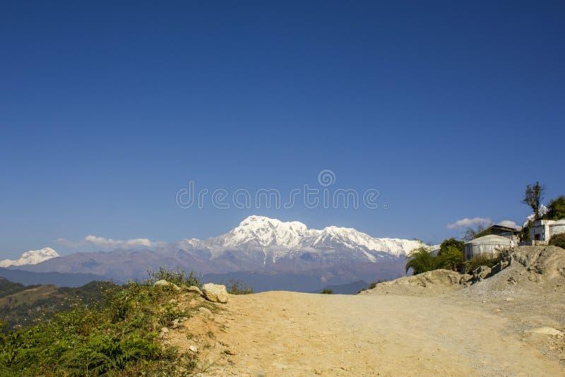 Een stoffige weg van de vuilberg op een achtergrond van schone blauwe hemel en bergen met sneeuwpieken royalty-vrije stock fotografie