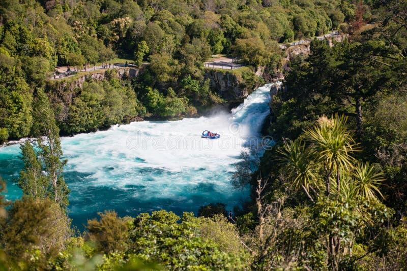 Een straalboot met toeristen in Huka valt, Nieuw Zeeland stock afbeelding